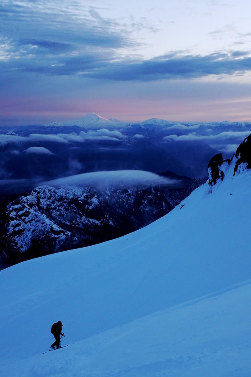 Deuxième tentative de l'ascension du Villarica, après des conditions météo défavorables... cette fois sera la bonne ! Les premières lueurs du matin éclairent joliment le Llaima, au fond.